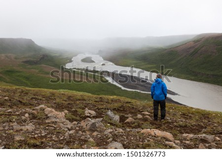 Iceland hiking concept. Single unidentified male traveler standing on the hill near Asbyrgi, Northern Iceland. Beautiful river solitude landscape. #1501326773