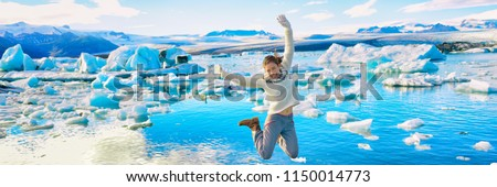 Iceland Jökulsárlón Glacier Lagoon tourist woman jumping of happiness - Icelandic touristic destination popular attraction. Panoramic banner. #1150014773