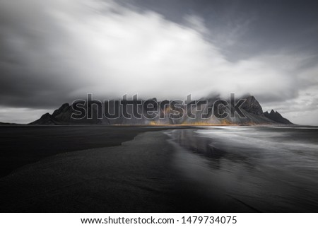 Iceland landscape picture from Stokksness in Northeast Iceland. Long exposure with ocean and cloud movement and an eerie looking mountain in the background