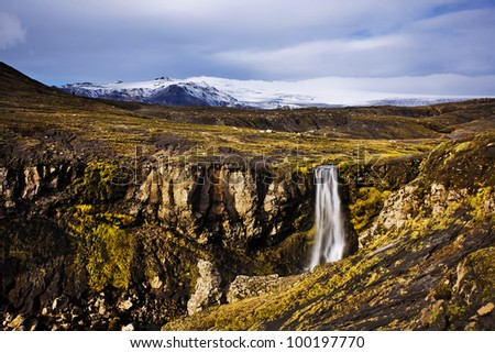 Iceland landscape, waterfall and famous Eyjafjallajokull volcano in background