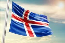 Iceland national flag cloth fabric waving on the sky with beautiful sun light