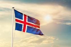 Iceland national flag cloth fabric waving on the sky with beautiful sun light - Image