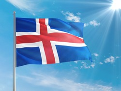 Iceland national flag waving in the wind against deep blue sky. High quality fabric. International relations concept.