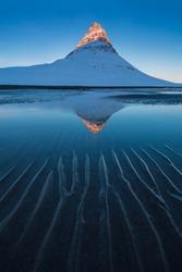 Iceland snaefellsnes peninsula and famous Kirkjufell. Kirkjufell is a beautifully shaped and a symmetric, free standing mountain in Iceland. Frozen view of Kirkjufell (church mountain). Winter season