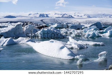 Iceland summer - Jokusarlon glacier lagoon with sun lit floating icebergs in center of the picture. The enormous Vatnajokull glacier in background. Blue  color dominates. Some white clouds above snow #1442707295