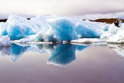 Iceland. The lagoon Jokulsaurloun. Cold early summer morning. White and blue icebergs and ice floes reflected in the smooth water. The concept of extreme, northern and photo tourism