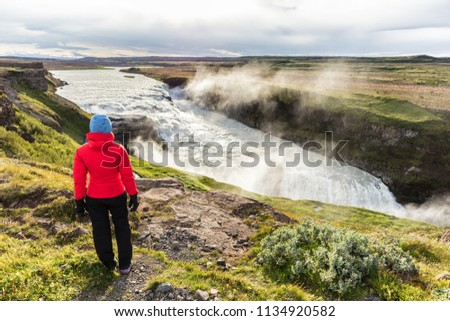 Iceland travel Gullfoss waterfall tourist woman looking over icelandic falls, famous attraction on the Golden circle. Nature lansdcape in summer, spring or autumn.