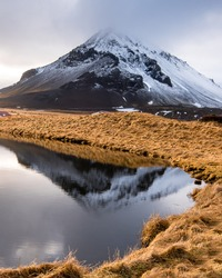 Icelandic dramatic landscape with lake and stapafell mountains covered in snow at snaefellsnes peninsula in Iceland. Icelandic landscapes.