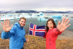 Icelandic flag - tourists on Jokulsarlon, Iceland on travel. Tourist couple happy holding showing Icelandic flag in front of the glacial lake / glacier lagoon.