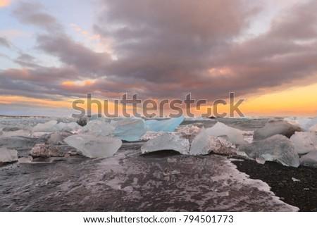 Stock Photo Icelandic glacier Jokulsarlon with icebergs on the beach at sunset
