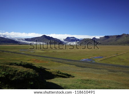 Icelandic Glacier over green fields against a blue sky