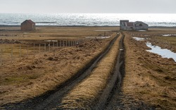 Icelandic meadow land with empty rural road leading to an abandoned farmhouse near the Atlantic Ocean.