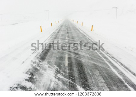 Icelandic road obscured by blowing snow in blizzard with electrical pylons in the distance #1203372838