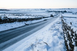 Icey and snow covered rural road, lined with dry stone walls, near Hexham in Northumberland National Park, England