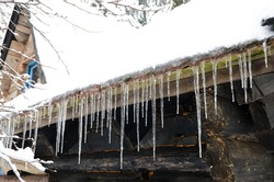 Icicle hanging off of a house. Winter landscape. Icicles hanging off roof rain gutter. Icicles hanging from frozen gutter of wooden cabin during cold morning.