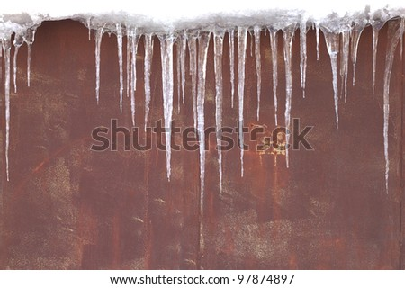 Icicles against a red-brown metal wall - stock photo