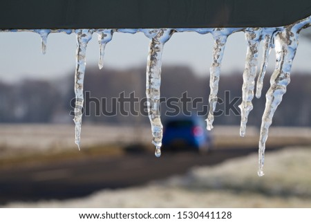 Icicles hang from a road sign as a blue car passes in the background. Drivers must exercise caution at this time of year to avoid losing control on slippery roads.