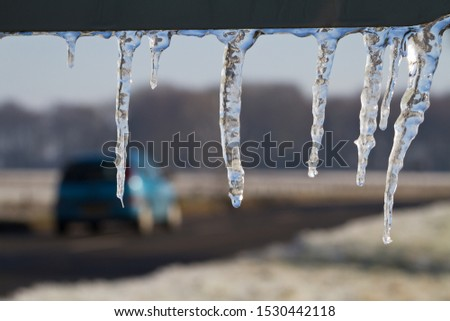 Icicles hang from a road sign as a green car passes in the background. Drivers must exercise caution at this time of year to avoid losing control on slippery roads.