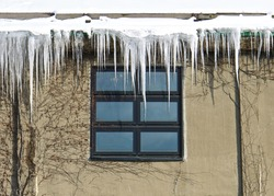 icicles hang from rain gutters on a chilly winter day