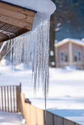 Icicles hang from the snowy roof of a mountain cottage