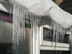 Icicles hanging from guttering on the roof of a sunroom, made from the sunlight melting the snow.