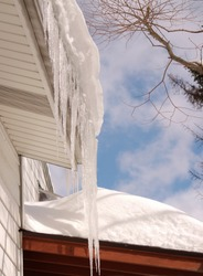 Icicles hanging from the eaves and thick snow on a roof