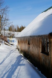 icicles hanging from the roof of wooden hut