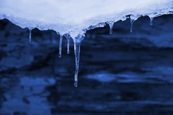 icicles hanging from the snowy roof, against the log walls