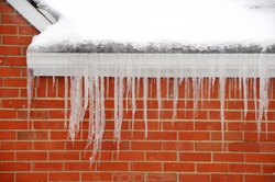 icicles hanging on side of house in winter