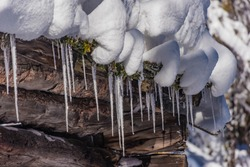 icicles on a snowy roof of an oad wooden barn