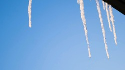 Icicles on background of blue sky. Concept. View from window of hanging clear icicles on clear day. Beautiful icicles over window on background of blue sky