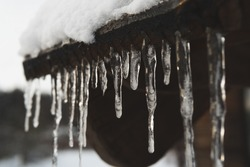 Icicles on roof with snow. Safety tips for icicles.