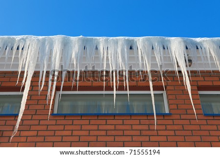 Icicles on the roof of a brick house