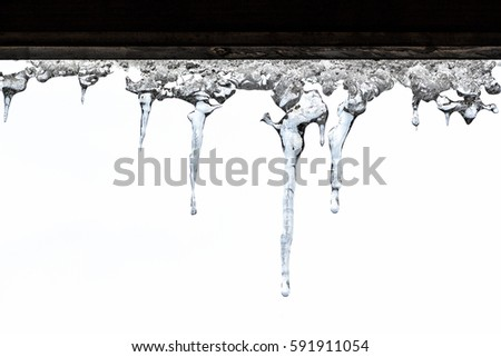 Shutterstock Icicles on the roof of a private farmhouse on a white background.