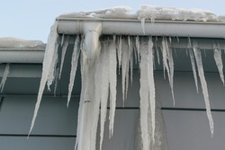 Icicles on the roof. The drain is full of snow and ice. Icicles falling danger concept.