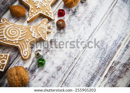 Icing decorated  gingerbread cookies with nuts and multicolored bells on white painted grunge style wooden table #255905203