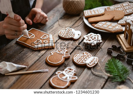 Icing of Christmas bakery. Woman decorating honey gingerbread cookies on wooden brown table. closeup, copy space. Blank biscuit gingerbread house, ready to decorate.