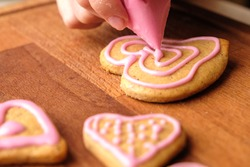 Icing of Valentines Day. Woman decorating gingerbread cookies in the shape of heart on a wooden table.