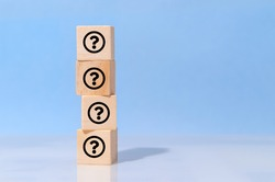 Icon question Mark on wooden cube block on blue background. FAQ, answer, information, communication and brainstorming concepts
