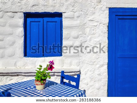 Iconic blue table with wooden chairs and window in front of Greek house, Greece