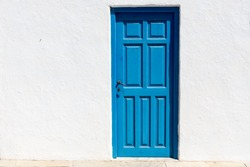 Iconic blue wooden door against clear white wall and colorful flowers. Typical view for Greek islands, Greece