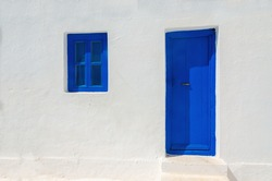 Iconic blue wooden door and window against clear white wall. Typical view for Greek islands, Greece