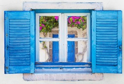 Iconic blue wooden window on white stone wall of typical Greek house, Greece