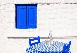Iconic Greek restaurant with blue tablecloth and wooden chairs in front of stone white wall, Greece