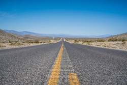 Iconic image of highway in Death Valley with beautiful blue sky. Infinitely long straight road surrounded by desert and mountains