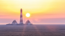 Iconic lighthouse of westerhever on North Sea coast of Germany at sunset