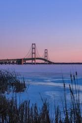 Iconic Mackinac bridge in frozen Lake Michigan under twilight