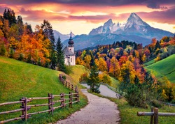 Iconic picture of Bavaria with Maria Gern church with Hochkalter peak on background. Fantastic autumn sunrise in Alps. Superb evening landscape of Germany countryside. Traveling concept background.