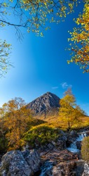Iconic Scottish mountain Buachaille Etive Mòr in the Highlands on a crisp clear autumn day with autumnal trees and dramatic waterfalls of the River Coupall in the foreground