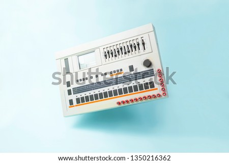 Iconic vintage Japanese analog drum-machine/ groove box, levitating on blue background. electronic music concept